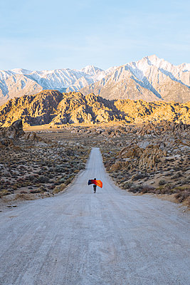 Woman with colourful blanket running down road in desert at sunrise, California, USA - p924m2153127 by Danielle Rodriguez