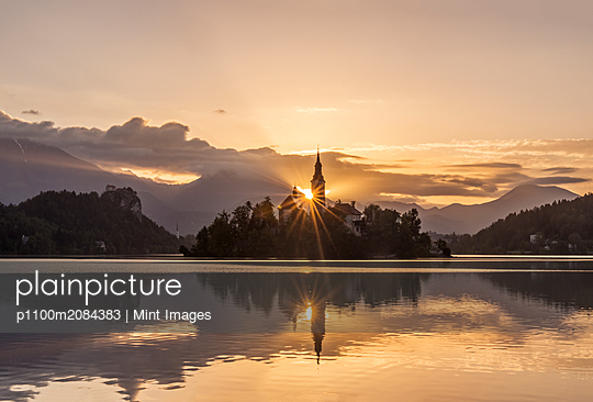 Sunrise over church tower reflected in still lake, Bled, Upper Carniola, Slovenia,Bled, Upper Carniola, Slovenia - p1100m2084383 by Mint Images