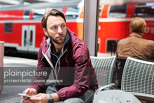 Mann wartet am Bahnhof und hört Musik - p1114m1159753 von Carina Wendland