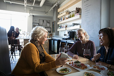Active senior women friends with smart phone talking, eating and drinking red wine in cafe - p1192m1567177 by Hero Images