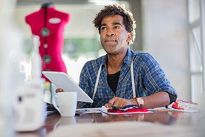 Fashion designer working with tablet on table - p300m1581162 von zerocreatives