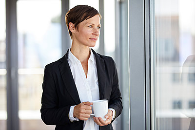 Businesswoman in office with cup of coffee  looking out of window - p300m2012963 by Rainer Berg