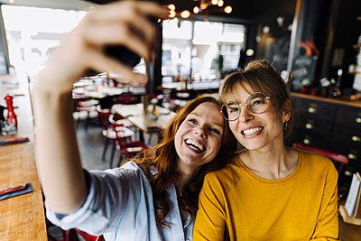 Two happy female friends taking a selfie in a restaurant - p300m2140512 von Kniel Synnatzschke