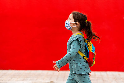 Girl walking with backpack and mask along red wall - p300m2198084 by Ezequiel Giménez