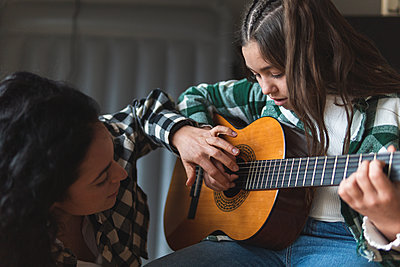 Mother teaching little daughter how to play acoustic guitar - p300m2265869 by Josu Acosta