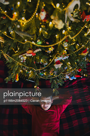 Happy boy lying under Christmas tree shot from above. - p1166m2084523 by Cavan Images