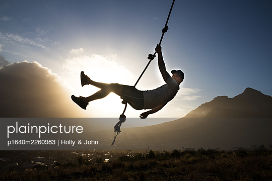 Sporty man swings on rope at sunset - p1640m2260983 by Holly & John