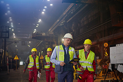 Supervisor and steelworkers walking and talking in steel mill - p1023m1519927 by Agnieszka Olek