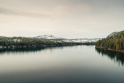 Scenic view of calm river against sky during winter - p1166m1417472 by Cavan Images