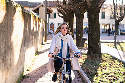 Female higher education student cycling on tree lined path - p429m2091482 by Francesco Buttitta