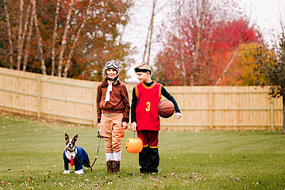 Portrait of boy, twin sister and boston terrier wearing halloween costumes in garden - p924m1513501 by Rebecca Nelson