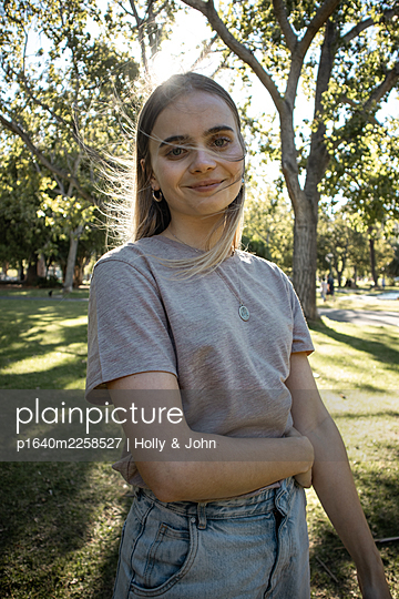 Portrait of teenage girl in a park - p1640m2258527 by Holly & John