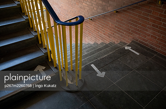Arrows as waymarkers in a staircase, Corona crisis - p267m2260768 by Ingo Kukatz