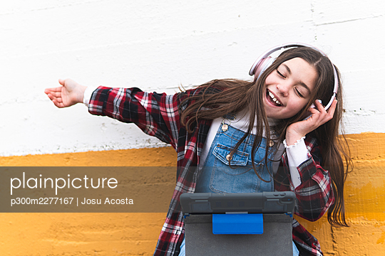 Cheerful girl listening music through headphones in front of wall - p300m2277167 by Josu Acosta