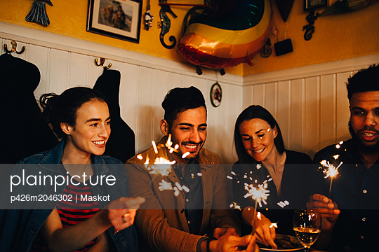 Happy young multi-ethnic male and female friends holding burning sparklers in restaurant during dinner party - p426m2046302 by Maskot