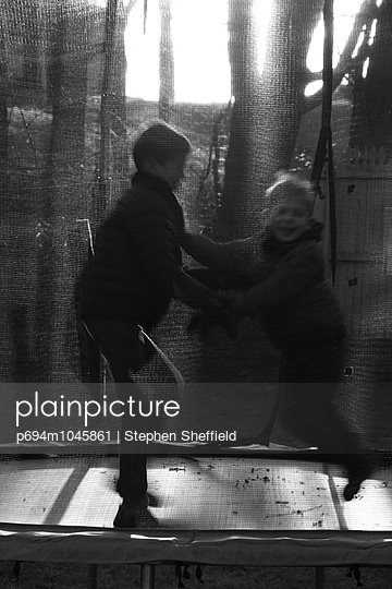 Two Boys Jumping on Trampoline - p694m1045861 by Stephen Sheffield