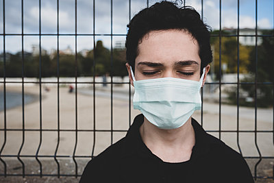 Portrait of a teenager wearing a mask eyes closed - p1166m2232488 by Cavan Images