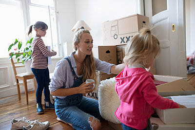 Mother and daughters packing moving boxes - p1192m2016830 by Hero Images