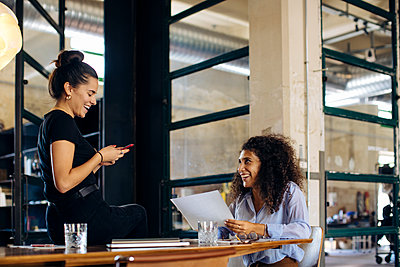 Two happy young businesswomen with smartphone in loft office - p300m2144807 by Sofie Delauw