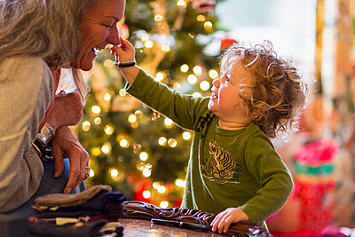 Caucasian grandmother and grandson playing with toys near Christmas tree - p555m1413721 by Marc Romanelli
