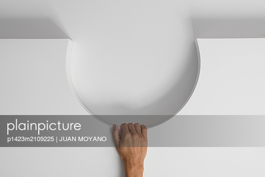 The hand of a young man leaning on a semicircle shaped hole on the wall - p1423m2109225 by JUAN MOYANO