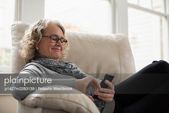 Senior woman relaxing on chair with mobile phone - p1427m2283139 by Roberto Westbrook