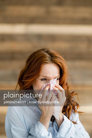 Redheaded woman blowing nose - p300m2140771 by Kniel Synnatzschke