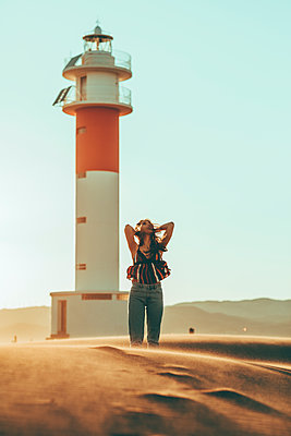 Young woman with windswept hair standing in desert landscape at lighthouse - p300m2005456 by Oriol Castelló Arroyo