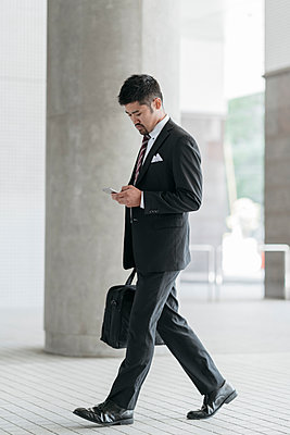 Young businessman with cell phone walking in the city - p300m2140128 by Juri Pozzi