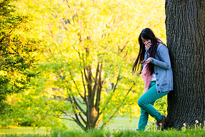 Young female laughing at mobile phone in park - p429m824433 by Florin Prunoiu