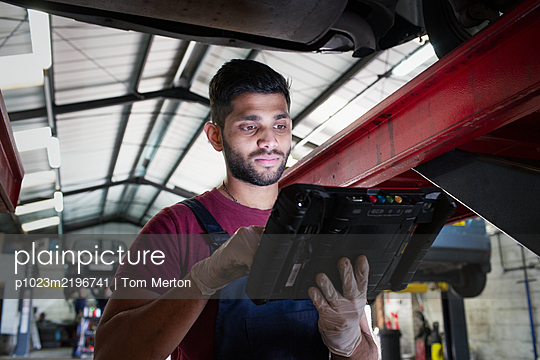 Focused male mechanic using diagnostic equipment in auto repair shop - p1023m2196741 by Tom Merton