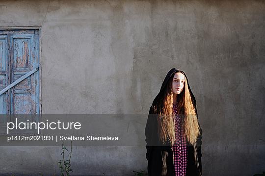 Frau vor einem Fenster mit geschlossenen Fensterläden - p1412m2021991 von Svetlana Shemeleva