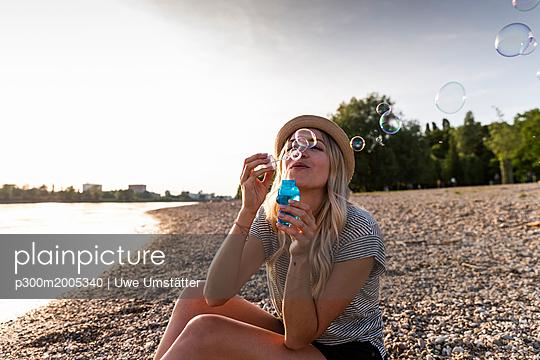 Blond woman blowing soap bubbles at riverside - p300m2005340 von Uwe Umstätter