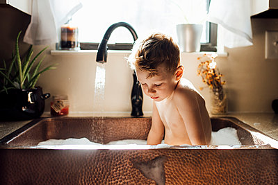 Shirtless boy taking bath while sitting in sink at home - p1166m2000806 by Cavan Images
