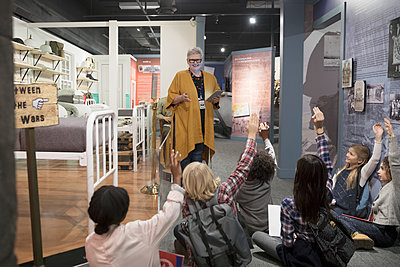 Students asking docent questions at exhibit on field trip in war museum - p1192m1447261 by Hero Images
