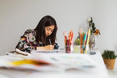 Illustrator painting at work desk in an atelier - p300m2058659 von VITTA GALLERY
