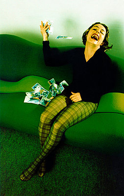 Laughing woman is throwing away old pictures - p567m720726 by Sandrine Agosti Navarri