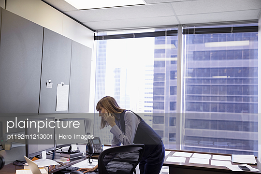 Female lawyer talking on cell phone and working at computer in office