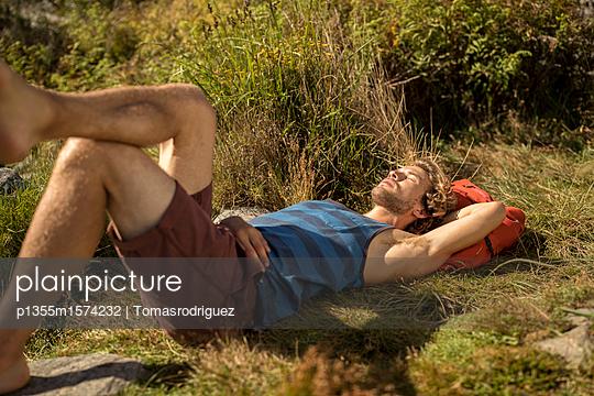 Junger Mann macht eine Pause beim Wandern - p1355m1574232 von Tomasrodriguez