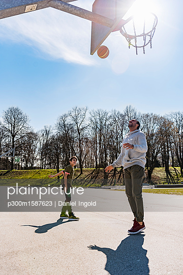 Father and son playing basketball on court outdoors - p300m1587623 von Daniel Ingold