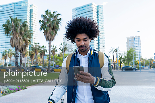 Casual businessman with bicycle using cell phone in the city, Barcelona, Spain - p300m2113801 von VITTA GALLERY