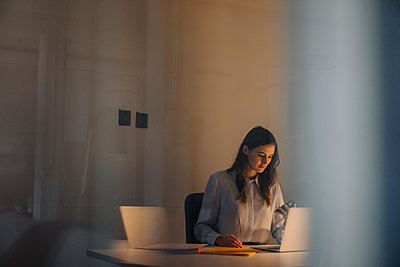 Young businesswoman working late at desk in office - p300m2103213 by Kniel Synnatzschke