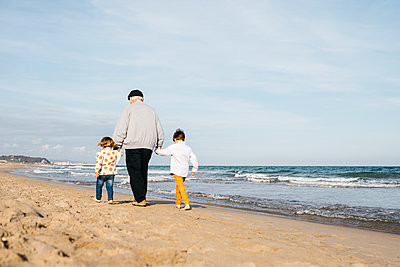 Back view of grandfather strolling with his grandchildren hand in hand on the beach - p300m2103273 von Josep Rovirosa