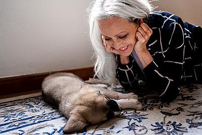 Smiling senior woman looking at dog sleeping on floor at home - p300m2287547 by Eloisa Ramos