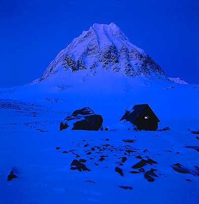 A cottage surrrounded by snow and mountain in the background at night - p3484699 by Greatshots