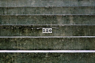Louisiana, New Orleans, Detail of an apartment address on a concrete staircase. - p442m936977f by Ray Laskowitz