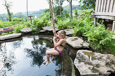 Caucasian girl swinging on rope above pool - p555m1419097 by Marc Romanelli