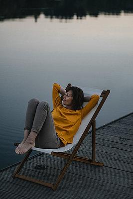 Reife Frau in einem Liegestuhl am Seeufer - p586m2109111 von Kniel Synnatzschke