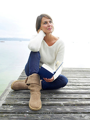 Frau liest Buch auf einem Steg  - p6430083 von senior images