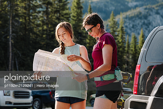 Female hikers looking at map in sunny parking lot - p1192m2129241 by Hero Images